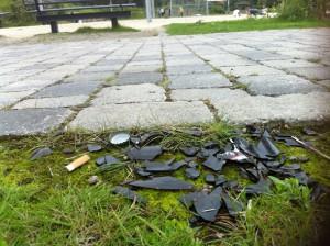 Bierflaschenscherben an Zigarettenkippen mit Blick auf Volleyballplatz.
