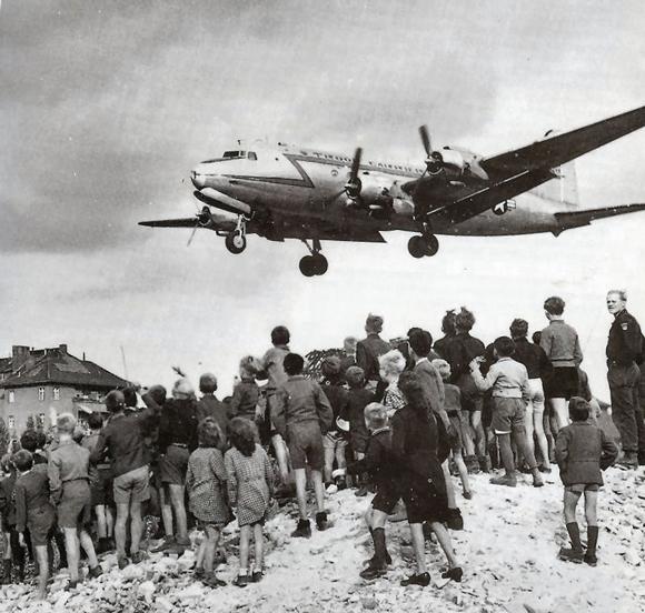 Berliner beobachten die Landung eines Rosinenbombers auf dem Flughafen Tempelhof (1948) Foto: USAF - United States Air Force Historical Research Agency via Cees Steijger Lizenz: Gemeinfrei