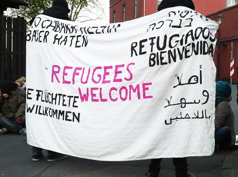 Transparent vor Flüchtlingsunterkunft. Schriftzug Flüchtlinge willkommen in verschiedenen Sprachen