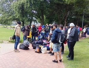 In Dortmund angekommene Geflüchtete warten mit Gepäck in einem Park