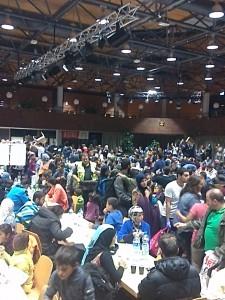 Mehrere hundert Menschen sitzen und stehen in der Halle der Anlaufstelle