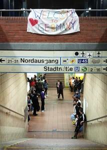"""Blick von einer Bahnsteigtreppe. Am Fuß der Treppe stehen Menschen, über der Treppenbrüstung hängt ein Transparent mit der Aufschrift Welcome to Germany""""."""