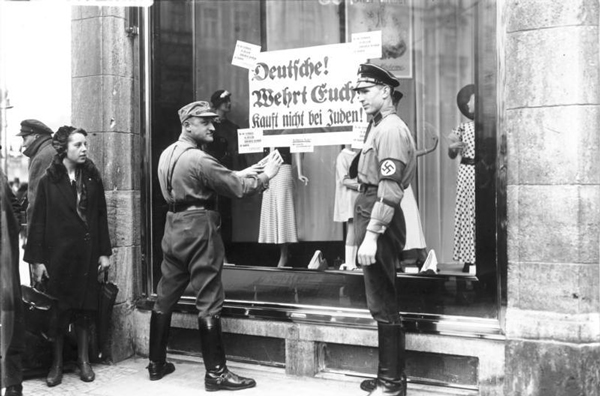SA-Mitglieder bekleben die Schaufenster eines jüdischen Geschäfts in Berlin oder Oldenburg Foto: Georg Pahl Lizenz: CC BY-SA 3.0 de