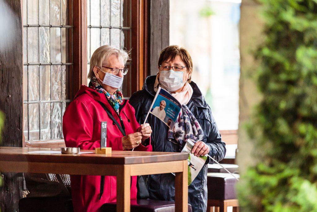 Sicherheit geht vor in Zeiten von COVID-19. Fans warten auf die Ankunft des Marathon-Paters - mit Mund-Nasen-Schutzmaske und Fähnchen; Foto: Tobias Appelt (Team Ruhr)