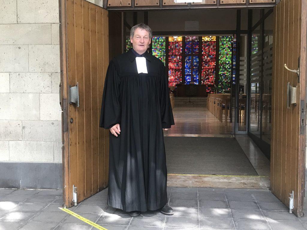 Pfarrer Jürgen Muthmann vor der Gnadenkirche; Foto: Peter Ansmann