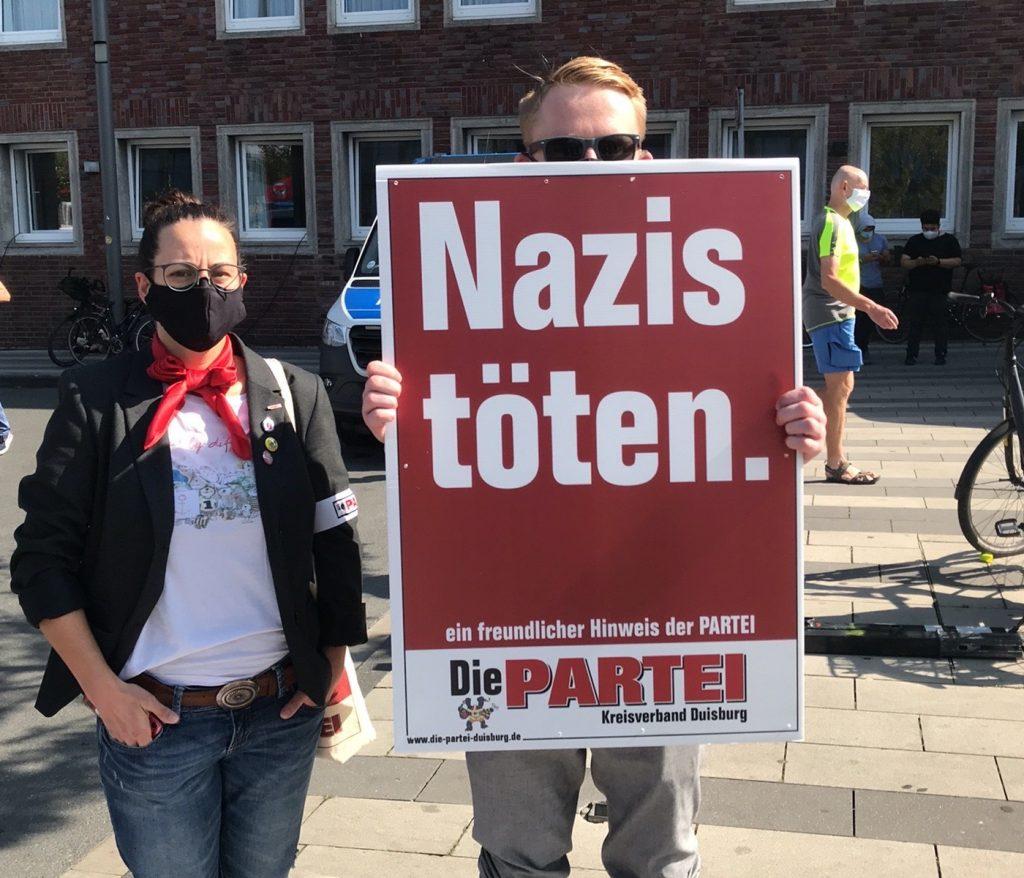 """Der """"graue Block"""" der PARTEI Duisburg (Sabine Hampe und Chris Fath) mit """"Nazis töten.""""-Plakaten; Foto: Peter Ansmann"""